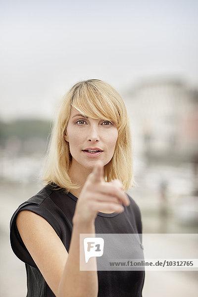 Porträt einer blonden Frau  die auf den Betrachter zeigt.