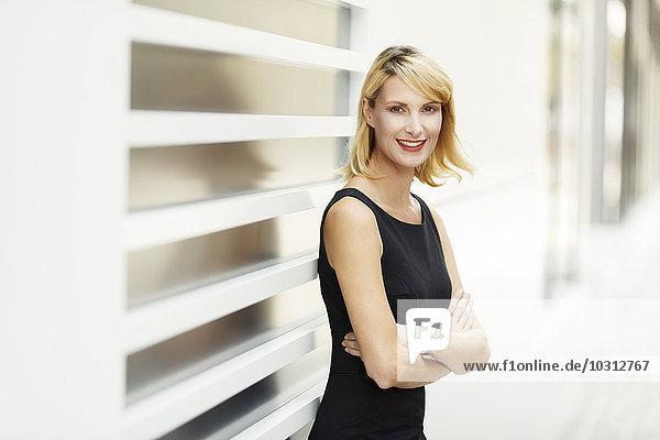 Porträt einer lächelnden blonden Frau mit gekreuzten Armen