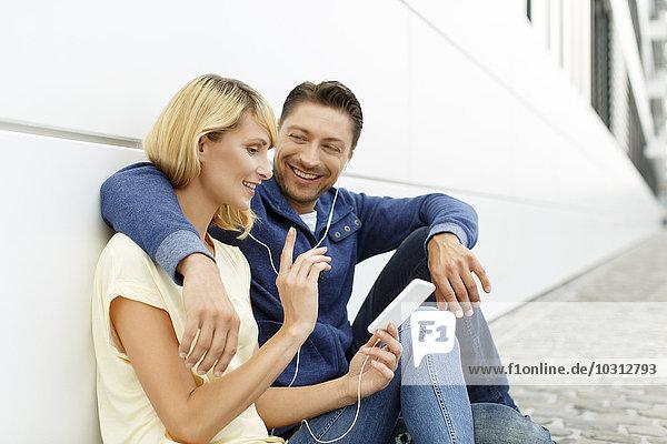 An die Fassade gelehntes Paar mit MP3-Player und Kopfhörer