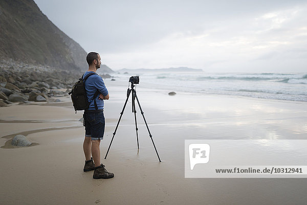 Spanien  Valdovino  Fotograf steht am Strand und fotografiert mit einem Stativ.