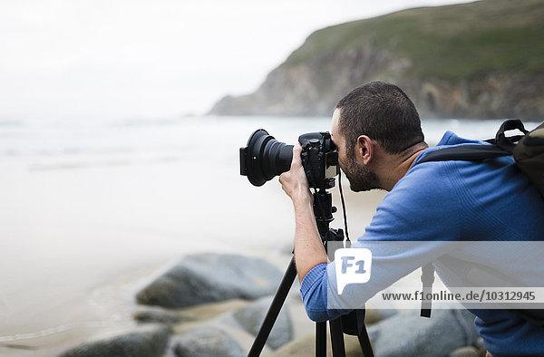 Spanien  Valdovino  Fotograf am Strand mit Stativ und Kamera