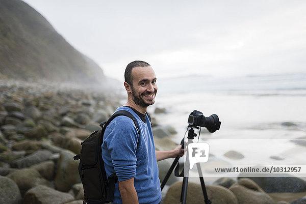 Spanien  Valdovino  Porträt des lächelnden Fotografen am Strand mit Stativ und Kamera