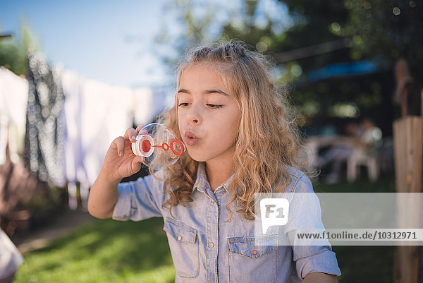 Kleines Mädchen bläst Seifenblasen