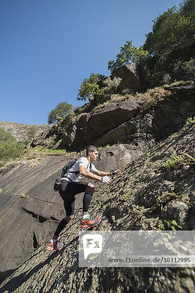 Spanien  Galizien  A Capela  Ultra Trail Runner auf einem Felshang