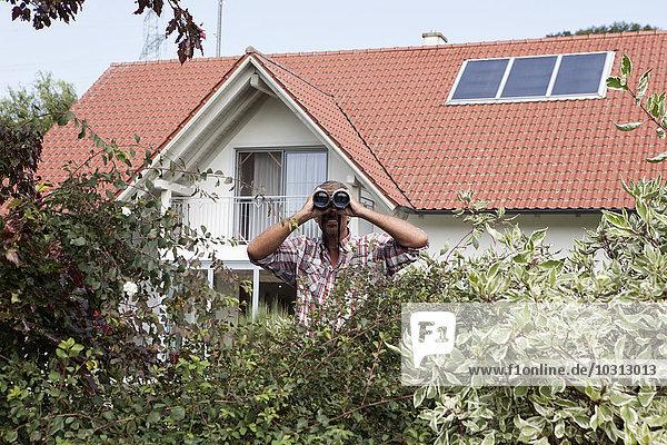 Mann schaut durchs Fernglas über Hecke