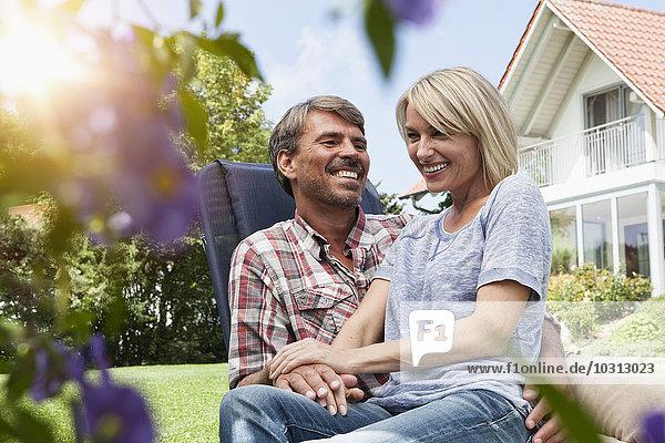Glückliches reifes Paar auf Liegestuhl im Garten