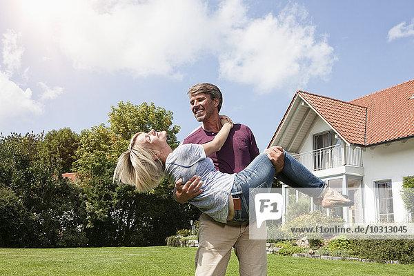 Glücklicher Mann mit Frau im Garten