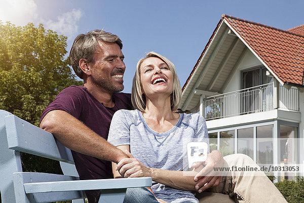 Glückliches reifes Paar auf Bank im Garten sitzend
