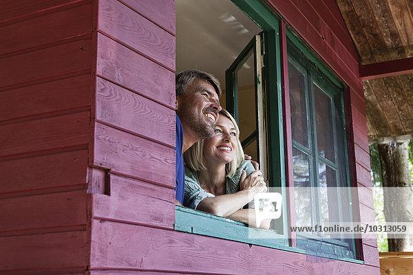 Glückliches reifes Paar  das aus dem Fenster des Sommerhauses schaut.