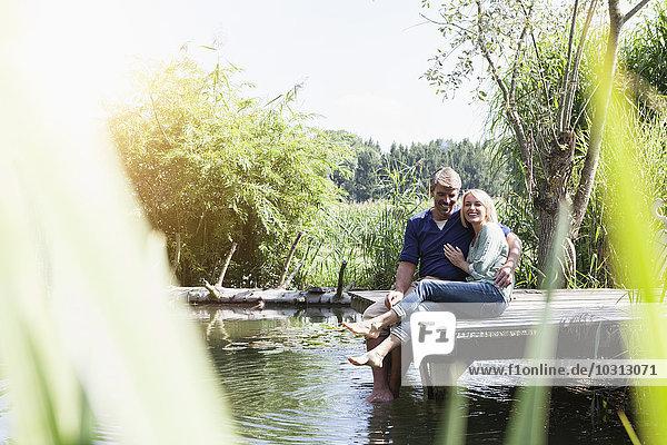 Glückliches reifes Paar am Steg eines Sees