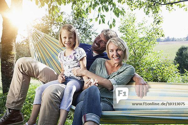Glückliche Familie sitzend in der Hängematte
