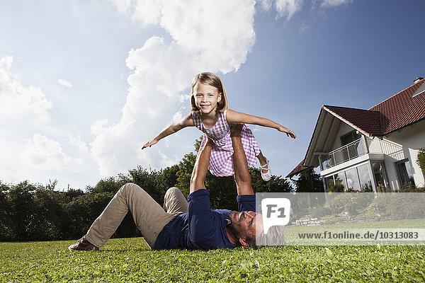 Vater spielt mit Tochter im Garten