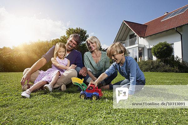 Glückliche Familie sitzt auf dem Rasen im Garten