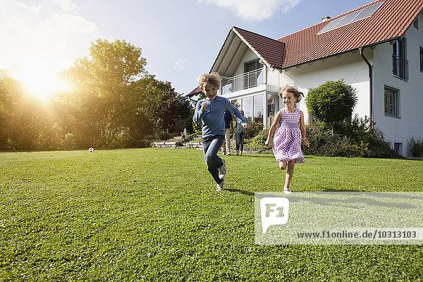 Bruder und Schwester laufen im Garten.