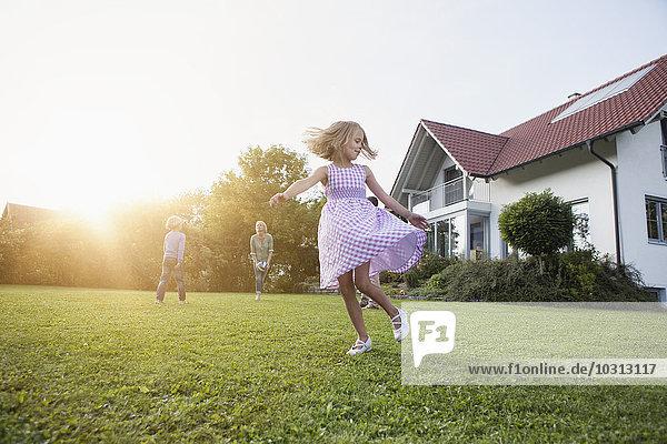 Mädchen in Bewegung mit Familie im Garten