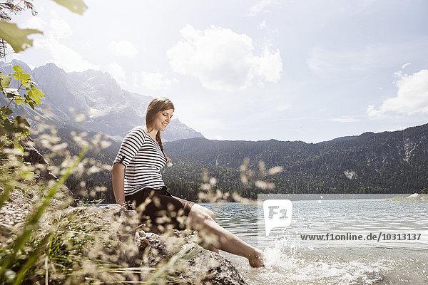 Deutschland  Bayern  Eibsee  lächelnde Frau beim Spritzen im Wasser