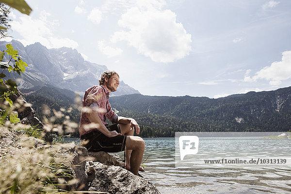 Deutschland  Bayern  Eibsee  lächelnder Mann in Lederhose sitzend am Seeufer