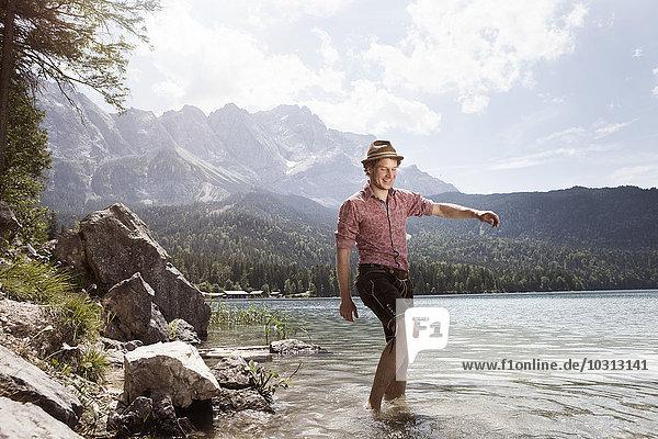 Deutschland  Bayern  Eibsee  glücklicher Mann in Lederhose  der im Wasser watet