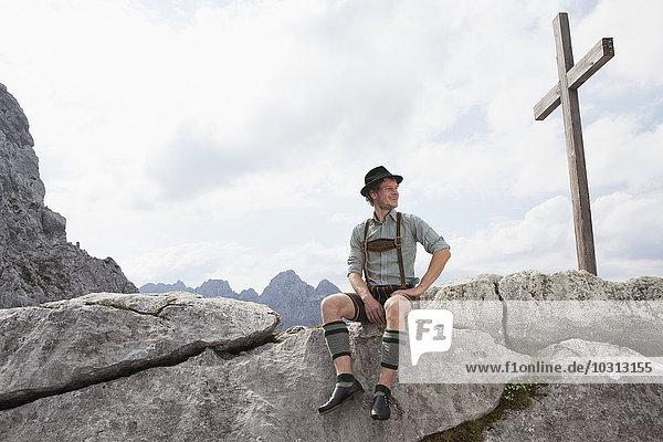 Deutschland  Bayern  Osterfelderkopf  Mann in traditioneller Kleidung am Gipfelkreuz sitzend