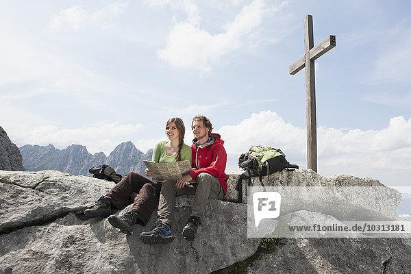 Deutschland  Bayern  Osterfelderkopf  Paar mit Landkarte am Gipfelkreuz