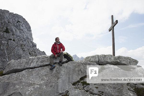 Deutschland  Bayern  Osterfelderkopf  Mann ruht am Gipfelkreuz