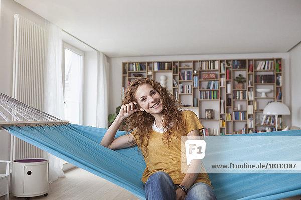Lächelnde Frau zu Hause in der Hängematte sitzend