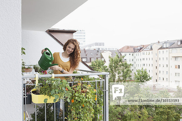 Lächelnde Frau beim Blumen gießen auf dem Balkon
