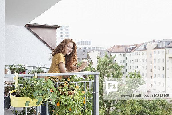 Lächelnde Frau mit Tasse Kaffee auf dem Balkon Lächelnde Frau mit Tasse Kaffee auf dem Balkon