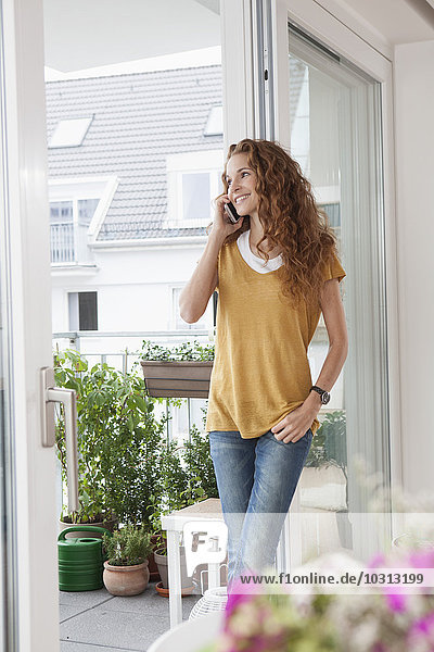 Lächelnde Frau mit Anlehnung an die Balkontür am Telefon