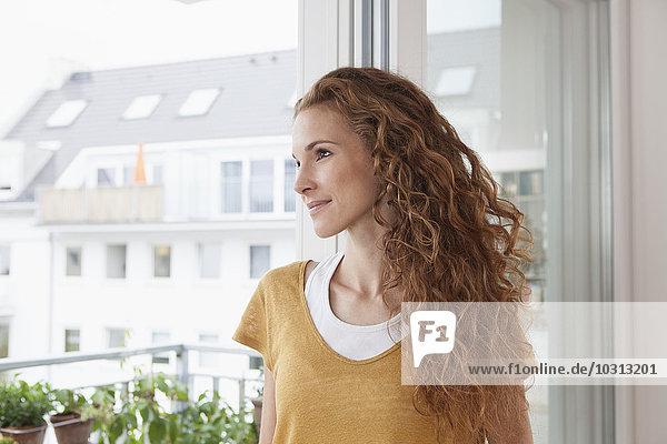Lächelnde Frau schaut aus dem Fenster