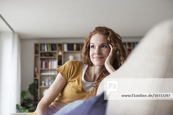 Lächelnde Frau zu Hause auf der Couch sitzend