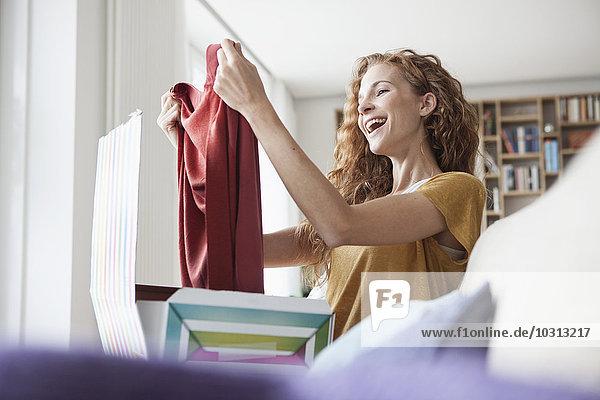 Glückliche Frau zu Hause auf der Couch sitzend  Paket mit Kleidungsstück auspackend