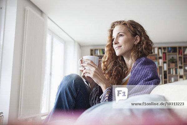 Frau zu Hause auf der Couch sitzend  Tasse haltend