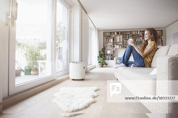 Lächelnde Frau zu Hause auf der Couch sitzend aus dem Fenster schauend