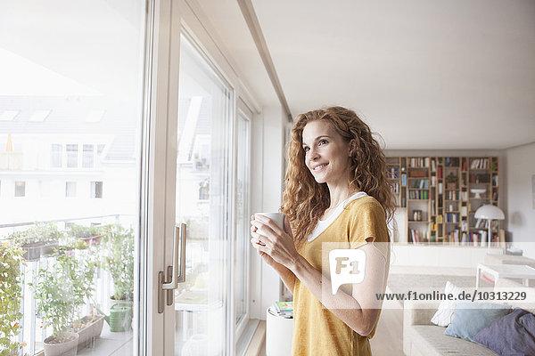 Lächelnde Frau zu Hause hält Tasse mit Blick aus dem Fenster