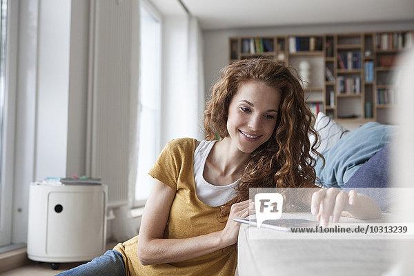Lächelnde Frau zu Hause mit digitalem Tablett auf der Couch