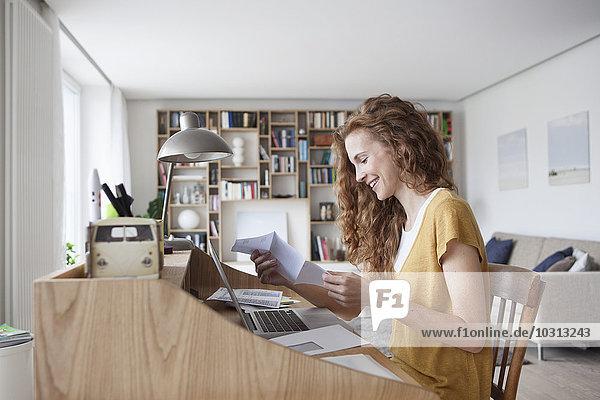 Frau zu Hause liest Brief auf Sekretärin Schreibtisch