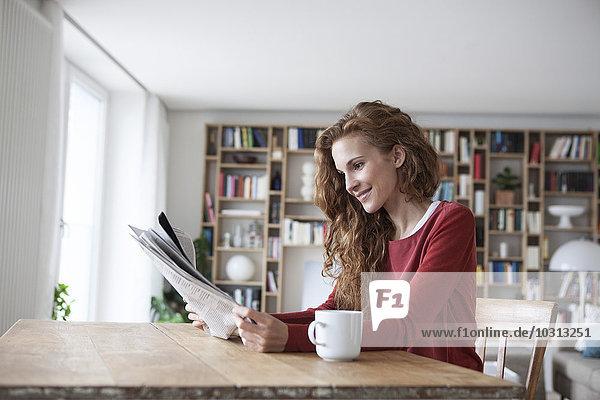 Lächelnde Frau zu Hause sitzend am Holztisch mit Tasse Zeitung lesen
