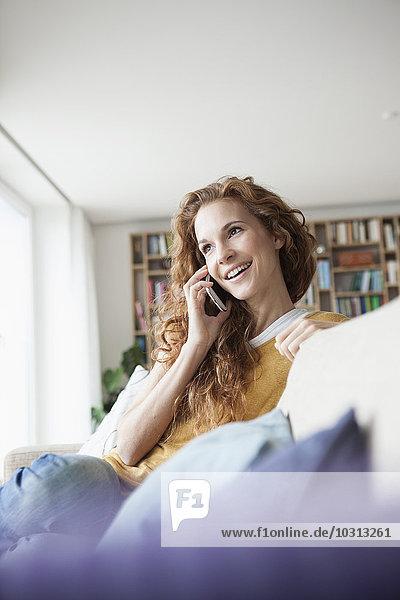 Lächelnde Frau zu Hause auf der Couch sitzend und mit dem Handy telefonierend