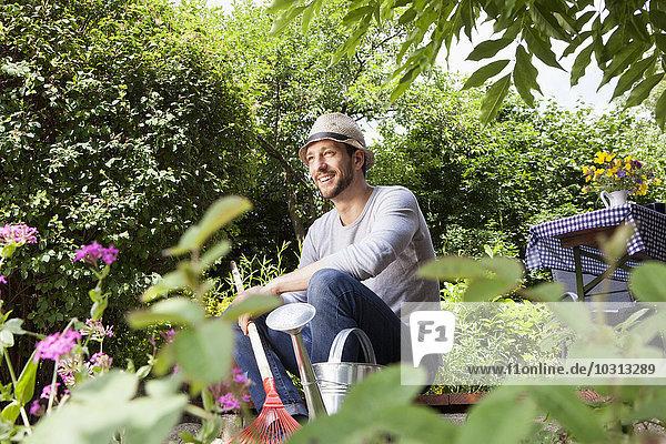 Lächelnder Mann sitzt auf der Gartenterrasse