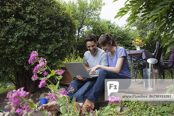 Glückliches Paar auf der Gartenterrasse mit Laptop