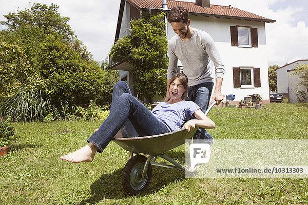 Verspieltes Paar mit Schubkarre im Garten