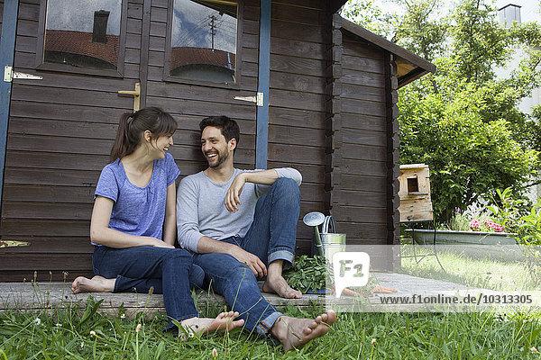Lächelndes Paar sitzend im Gartenhaus