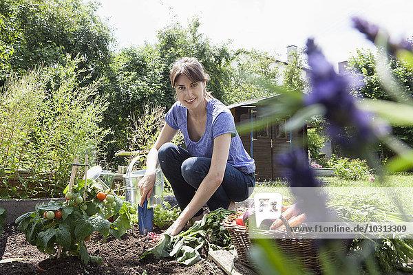 Lächelnde Frau im Garten im Gemüsebeet