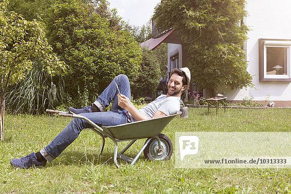 Lächelnder Mann in Schubkarre im Garten liegend
