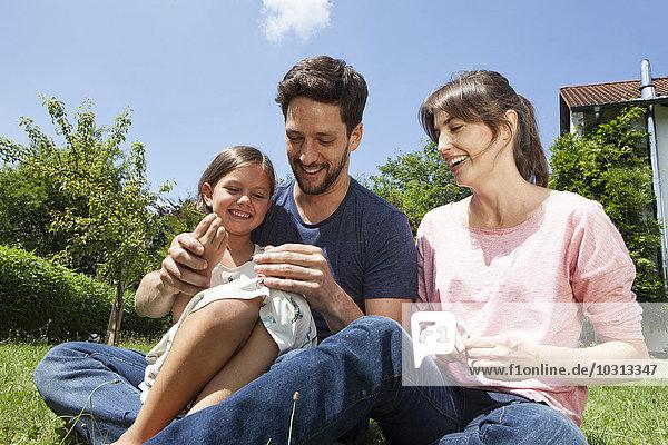 Glückliche Familie mit Tochter im Garten