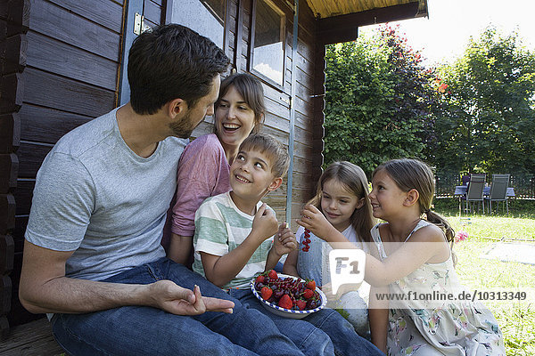Glückliche Familie beim Beerenessen im Gartenhaus