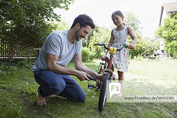 Vater bläst das Fahrrad der Tochter auf