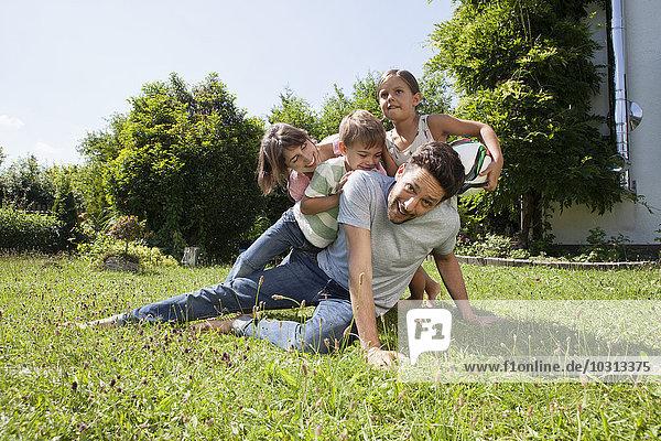 Verspielte vierköpfige Familie im Garten