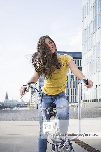 Deutschland  Köln  Porträt einer lächelnden jungen Frau mit blasenden Haaren auf dem Fahrrad